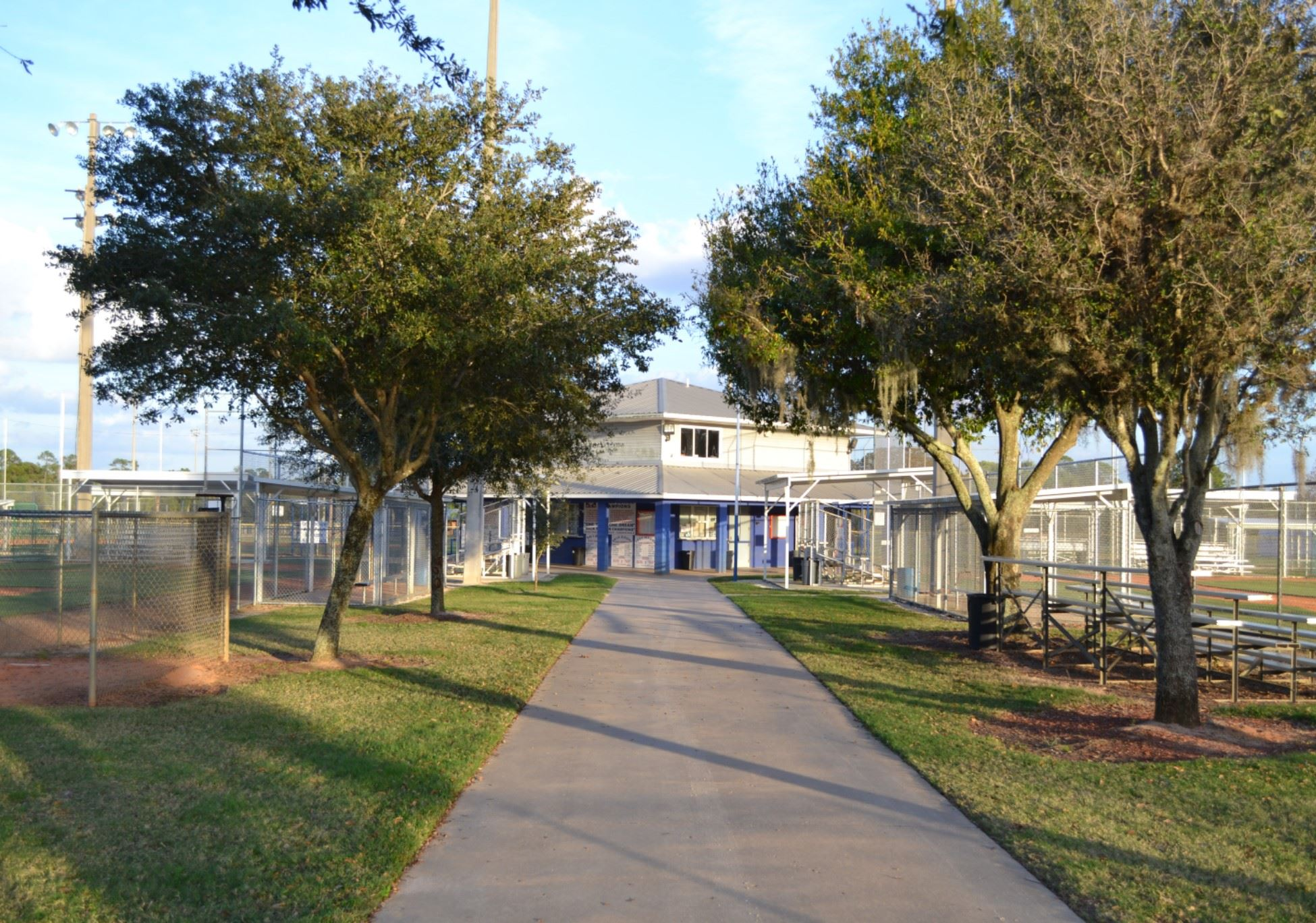 view walking up the sidewalk toward the baseball fields and concession stand
